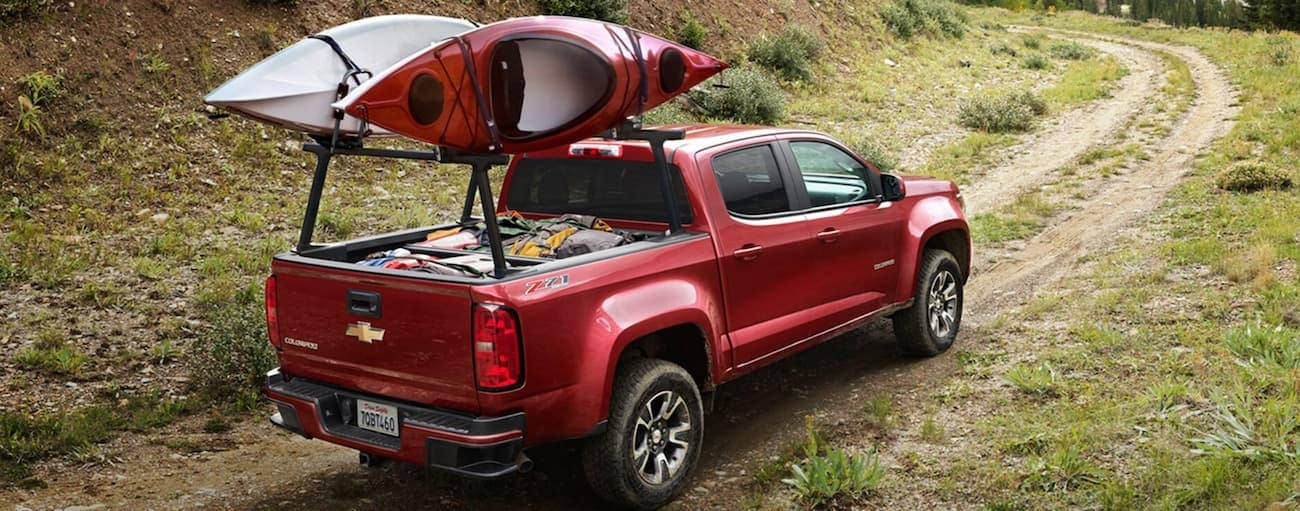 A red 2020 Chevy Colorado is driving on a dirt road with kayaks on the bed racks.