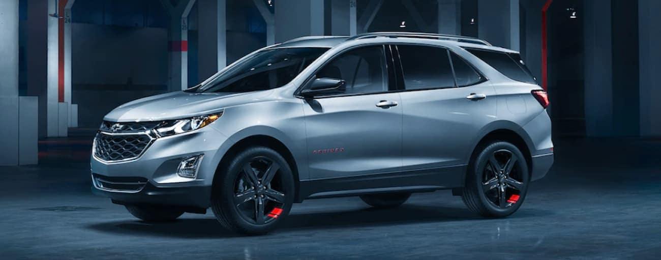 A silver 2020 Chevy Equinox Redline Edition is parked inside a dark lit garage near Cincinnati, OH.
