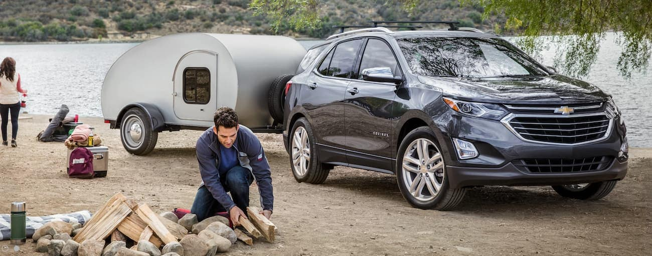 A couple is setting up their camp site while their 2020 Chevy Equinox has a small camper on the tow hitch.