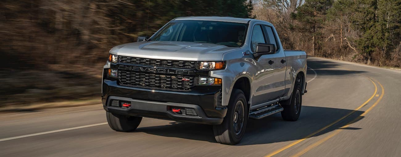 A grey 2020 Chevy Silverado 1500 Custom Trail Boss is driving around a corner past trees.