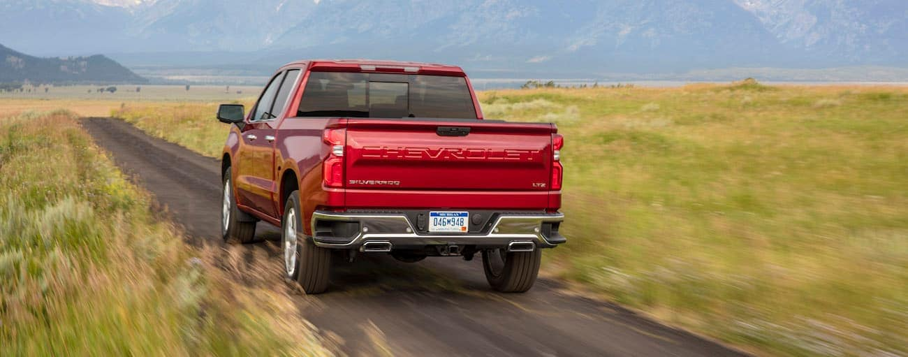 A red 2020 Chevy Silverado 1500 LTZ is driving on a dirt road through a field.