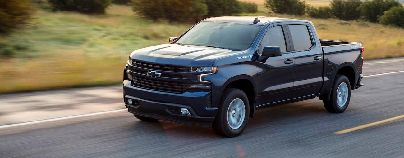 A blue 2020 Chevy Silverado 1500 RST is driving alone past blurred grass and bushes.