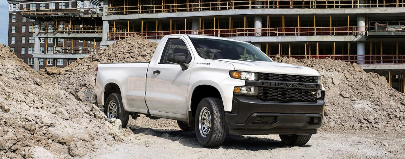 A white 2020 Chevy Silverado 1500 Work Truck is driving through a construction site in Cincinnati, OH.