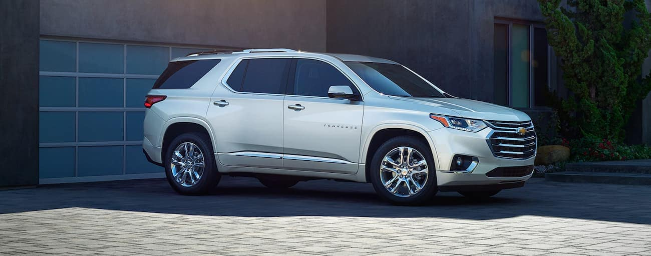 A white 2020 Chevy Traverse High Country is parked in front of a garage door.