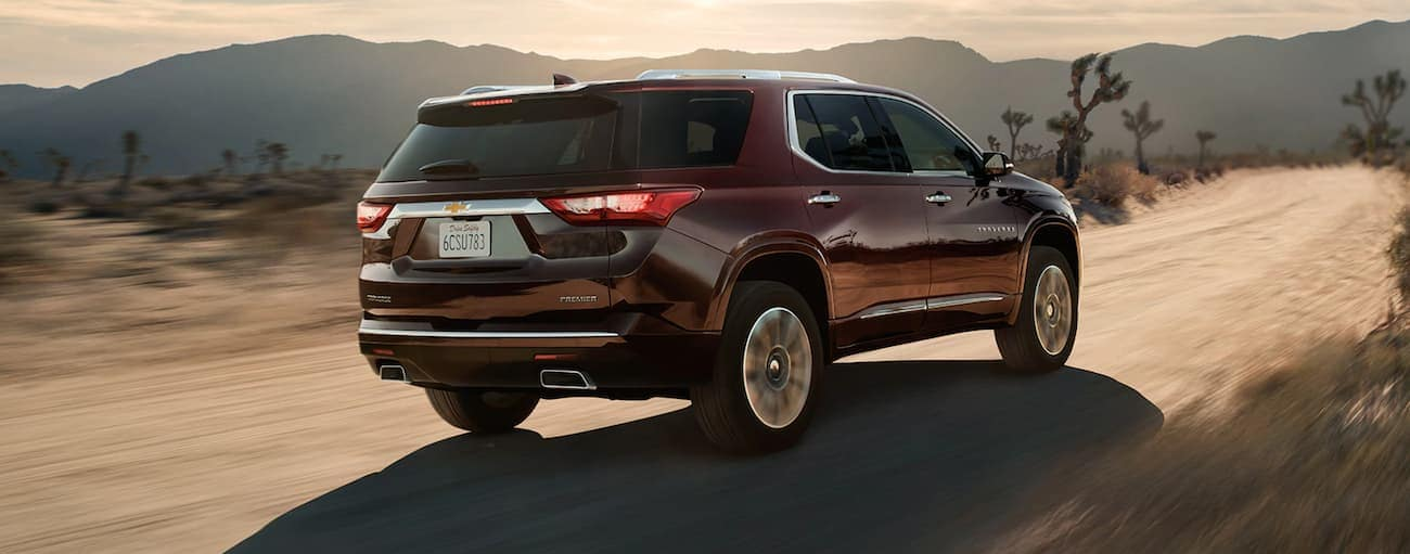 A burgundy 2020 Chevy Traverse Premier is driving on a desert road.