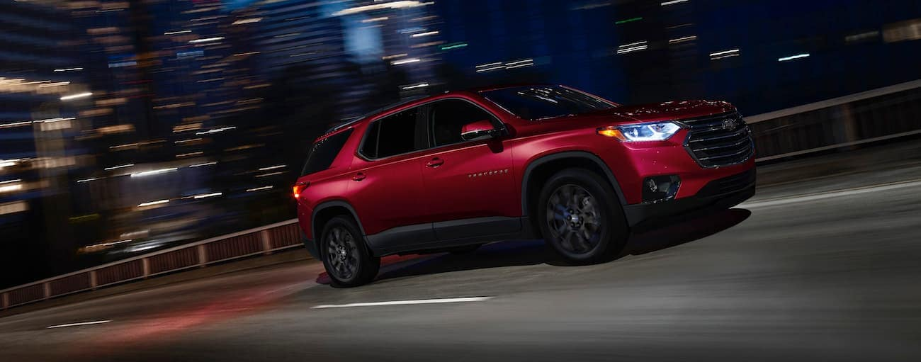 A red 2020 Chevy Traverse RS is driving past Cincinnati, OH, buildings at night.