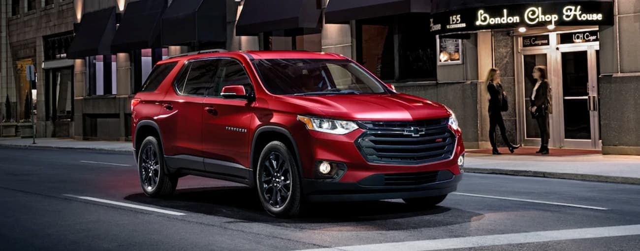 A red 2020 Chevy Traverse RS is on a city street at night.