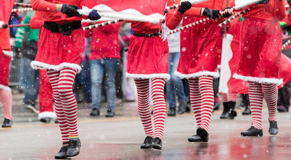 People dressed in red and white are walking in a Christmas parade near Columbus, OH.