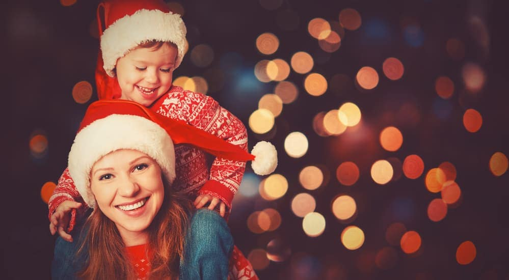 A mother has her son on her shoulders with blurred Christmas lights behind them.