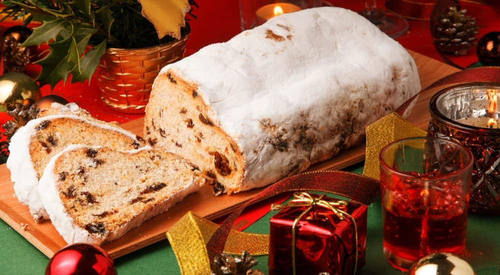 A German baked good, stollen, is shown in front of Christmas presents and lights.
