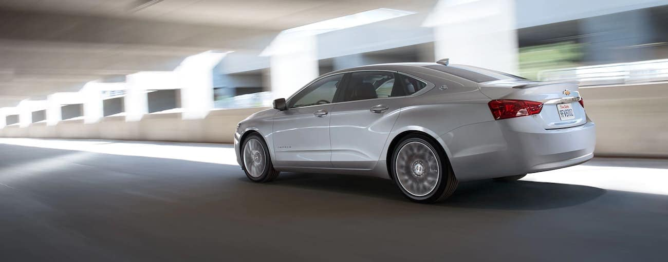 A silver 2020 Chevy Impala is driving under a highway overpass near Cincinnati, OH.