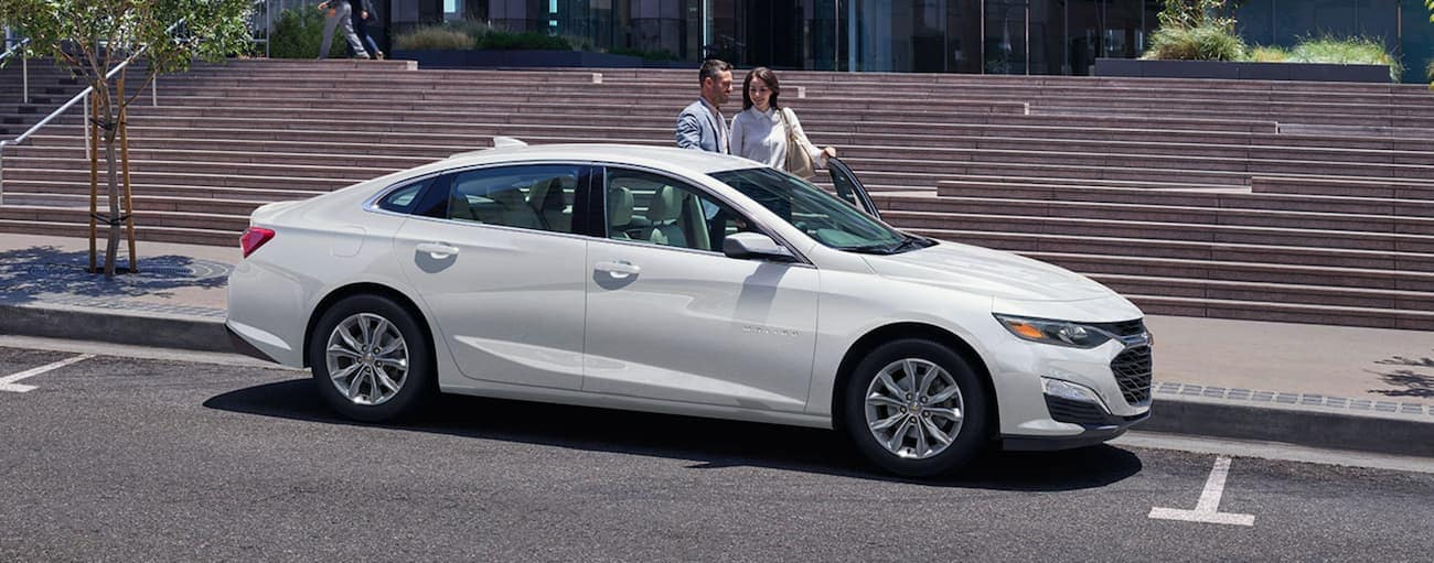 A couple is getting in to a white 2020 Chevy Malibu LT in front of city steps in Cincinnati, OH.