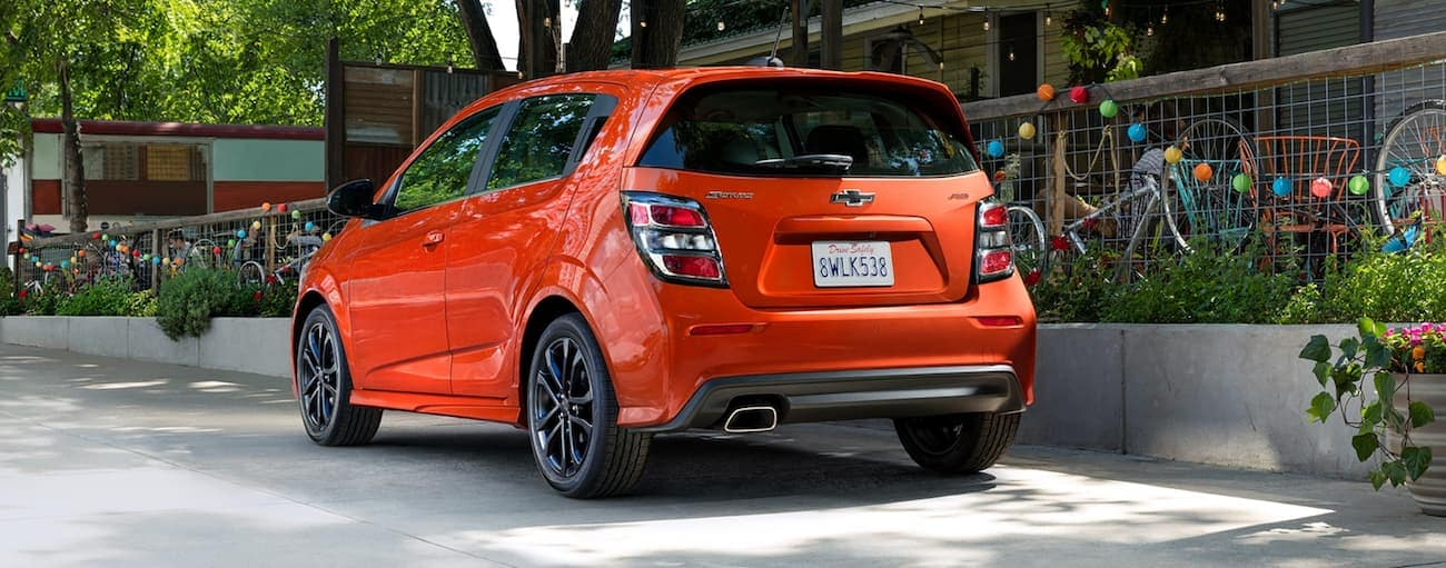 An orange 2020 Chevy Sonic is parked in front of a restaurant.