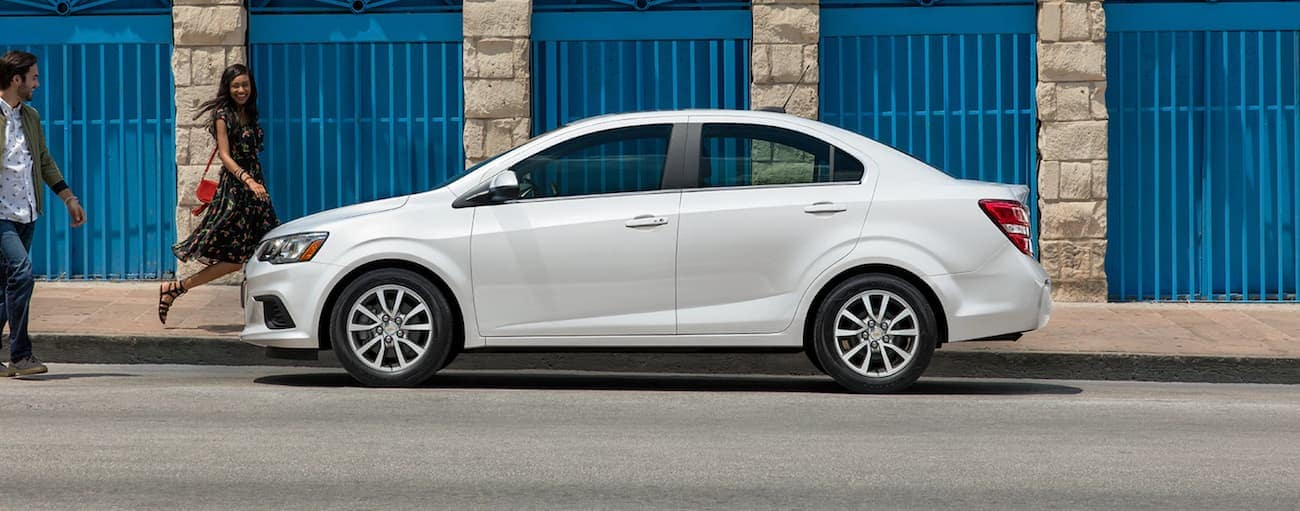 A white 2020 Chevy Sonic is parked in front of a stone building with blue doors.