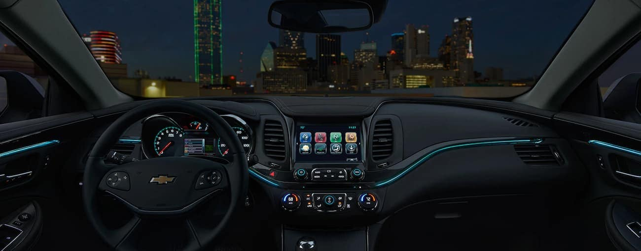 The front black leather interior of a 2020 Chevy Impala is shown at night.