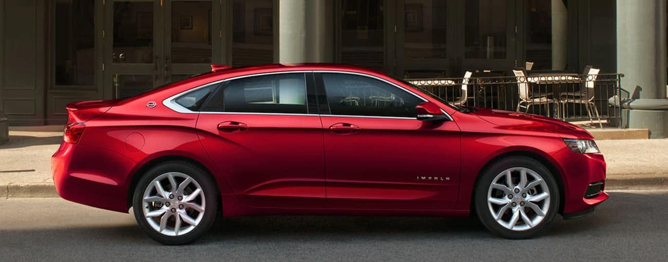 A red 2020 Chevy Impala is parked in front of a restaurant near Cincinnati, OH.