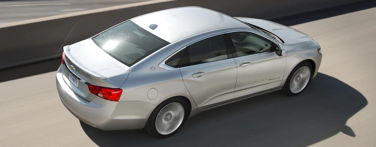 A birds eye view of a silver 2020 Impala is driving on a Cincinnati, OH, highway during the day.