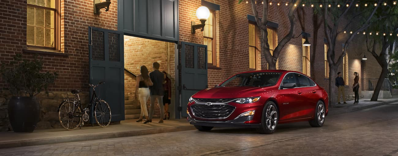 A red 2020 Chevy Malibu is parked in front of a lit up restaurant at night.