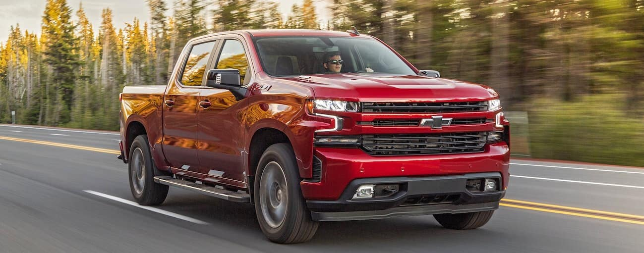 A red 2020 Chevy Silverado 1500, which wins when comparing the 2020 Chevy Silverado 1500 vs 2020 Ram 1500, is driving on a treelined road.