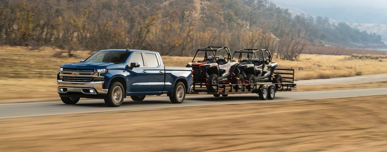 A blue 2020 Chevy Silverado is towing two side-by-sides on a trailer on a misty day.