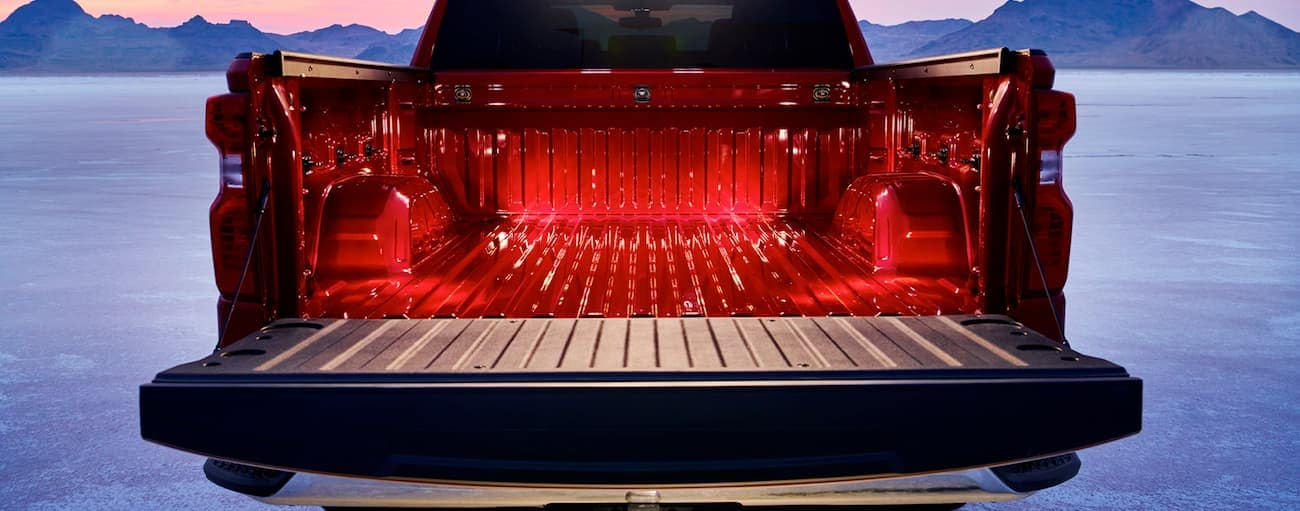 The tailgate is open on a red 2020 Chevy Silverado showing an illuminated bed.