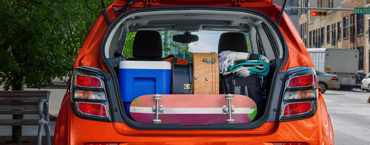 The tailgate of a 2020 Sonic is open showing the trunk packed with guitars, a skateboard and picnic gear.