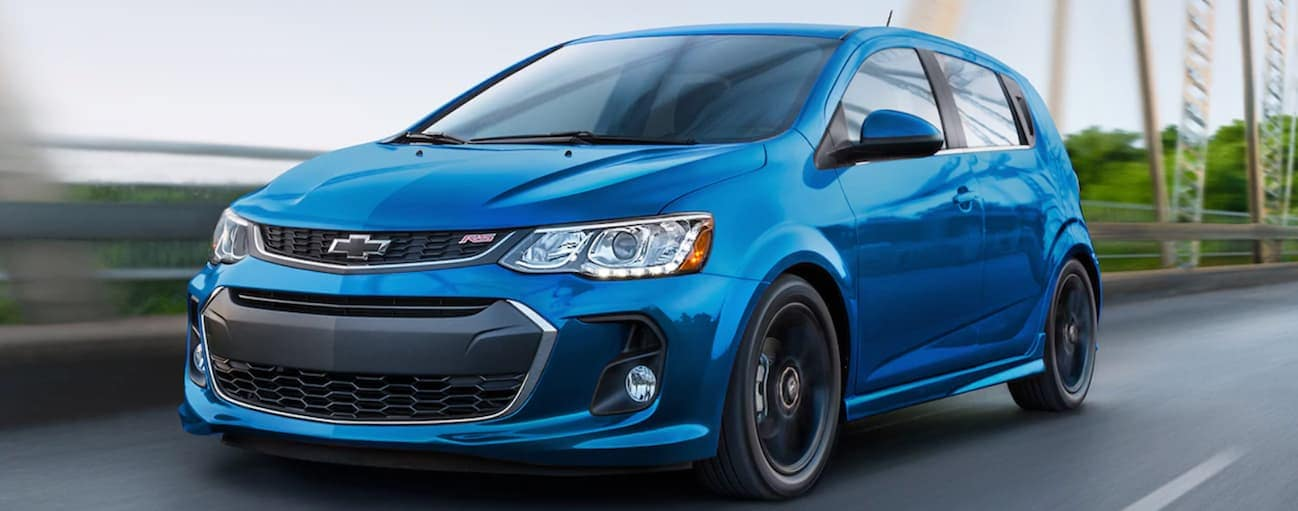 A blue 2020 Chevy Sonic hatchback RS is driving on a bridge.
