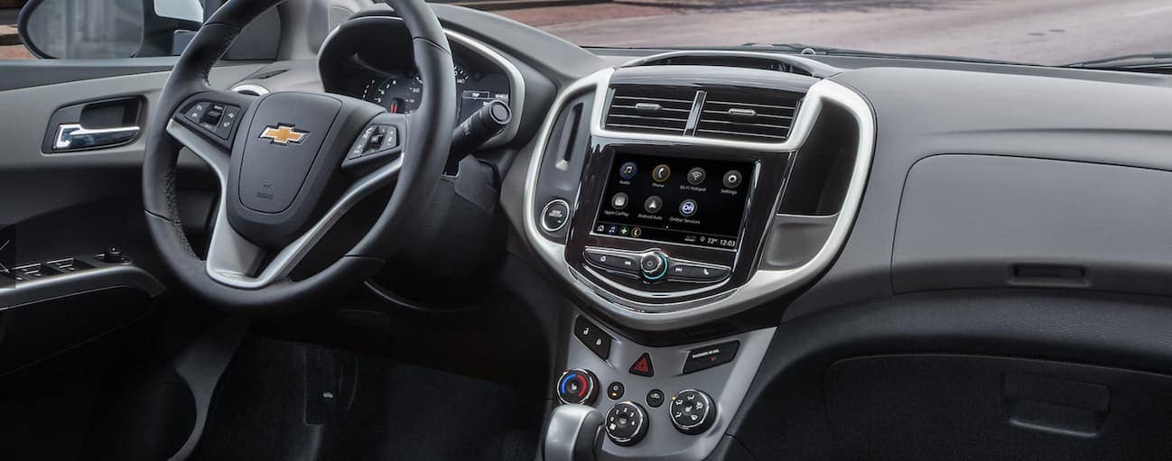 The front black leather interior of a 2020 Chevy Sonic is shown.