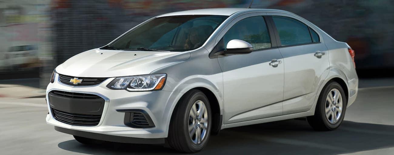 A silver 2020 Chevy Sonic sedan is driving past blurry buildings near Cincinnati, OH.