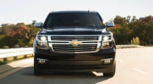A black 2020 Chevy Suburban is facing forward while driving on a tree lined highway near Cincinnati, OH.
