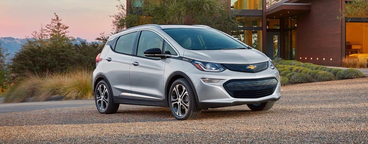 A silver 2021 Chevy Bolt EV is parked in front of a modern house.