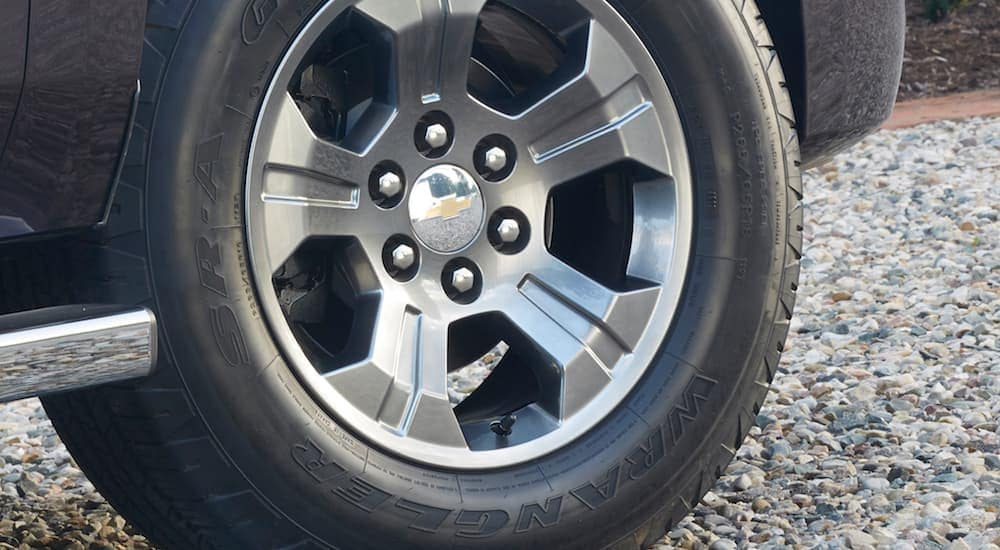A close up of a tire on a silver Chevy rim is shown.