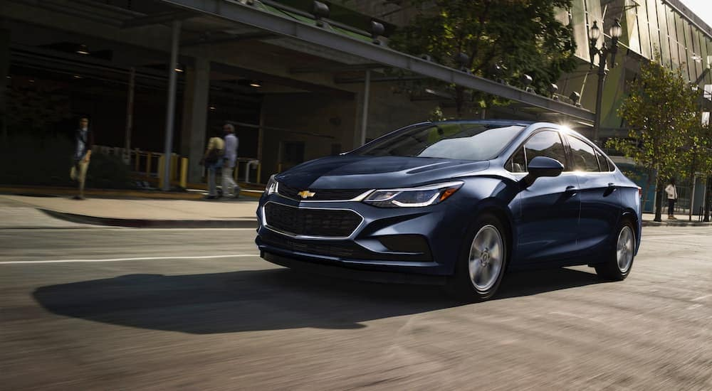 A blue 2018 Chevy Cruze, popular among used cars for sale in Ohio, is driving along a Cincinnati Street.