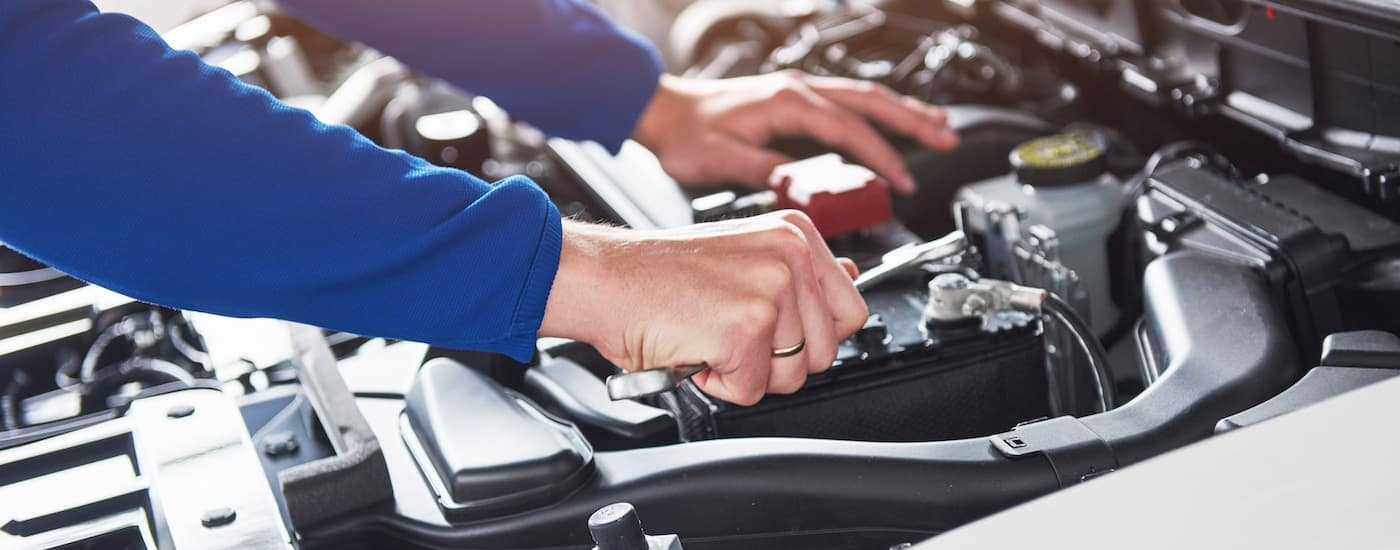 A mechanic is working under the hood of a used car.