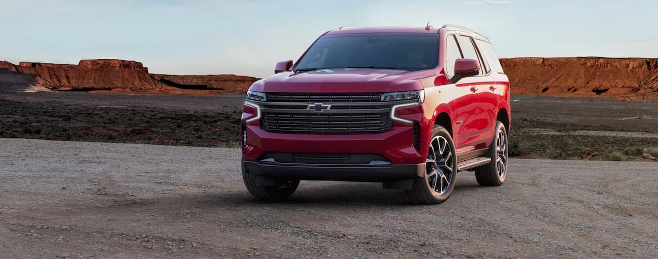 A red 2021 Chevy Tahoe is parked in a dirt parking lot with mountains in the distance.