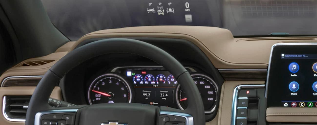 The drivers view of the black leather steering wheel and drivers head-up display is shown.
