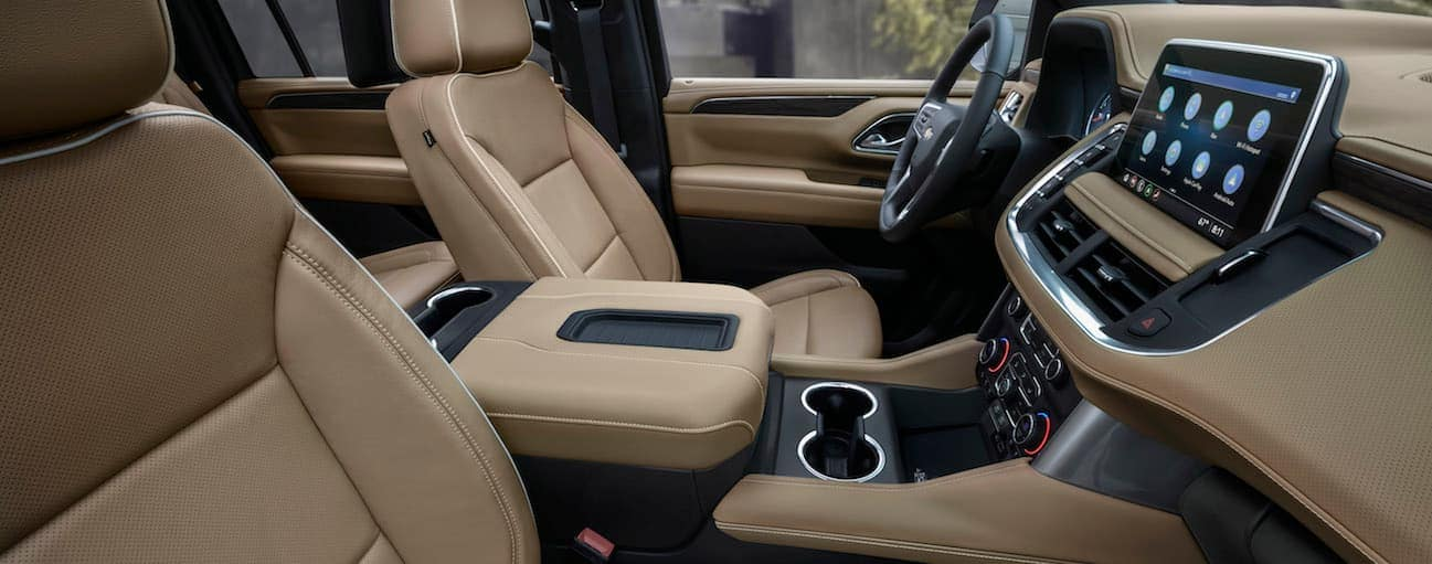 The front tan leather interior of a 2021 Chevy Suburban is shown from the side with an infotinament system.