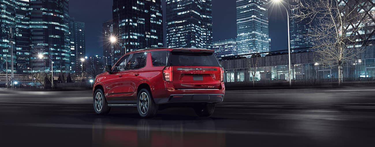 A red 2021 Chevy Tahoe RST is driving on road towards a city skyline near Cincinnati, OH, at night.