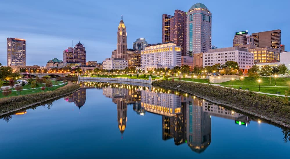 The Columbus, OH, city skyline is shown at dusk.