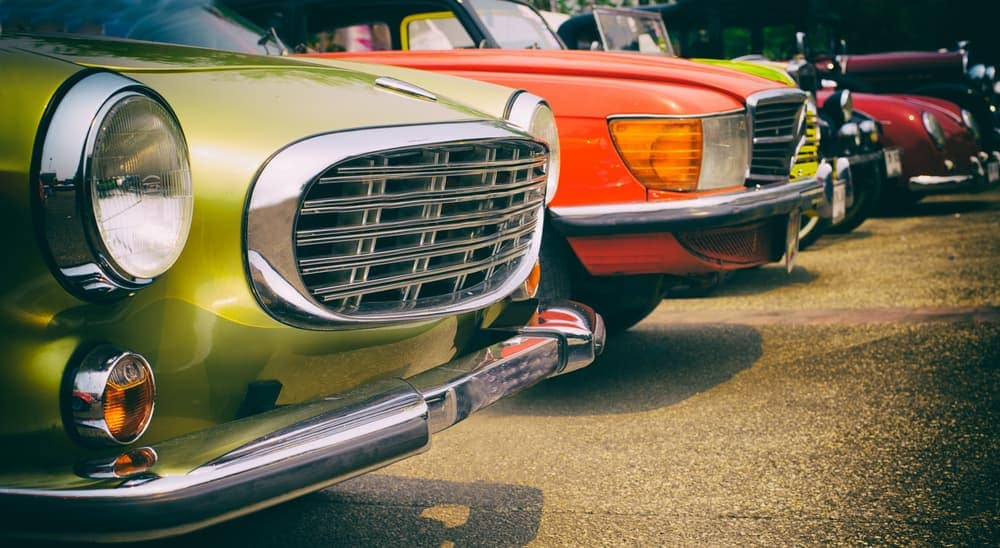 A row of classic cars is shown.