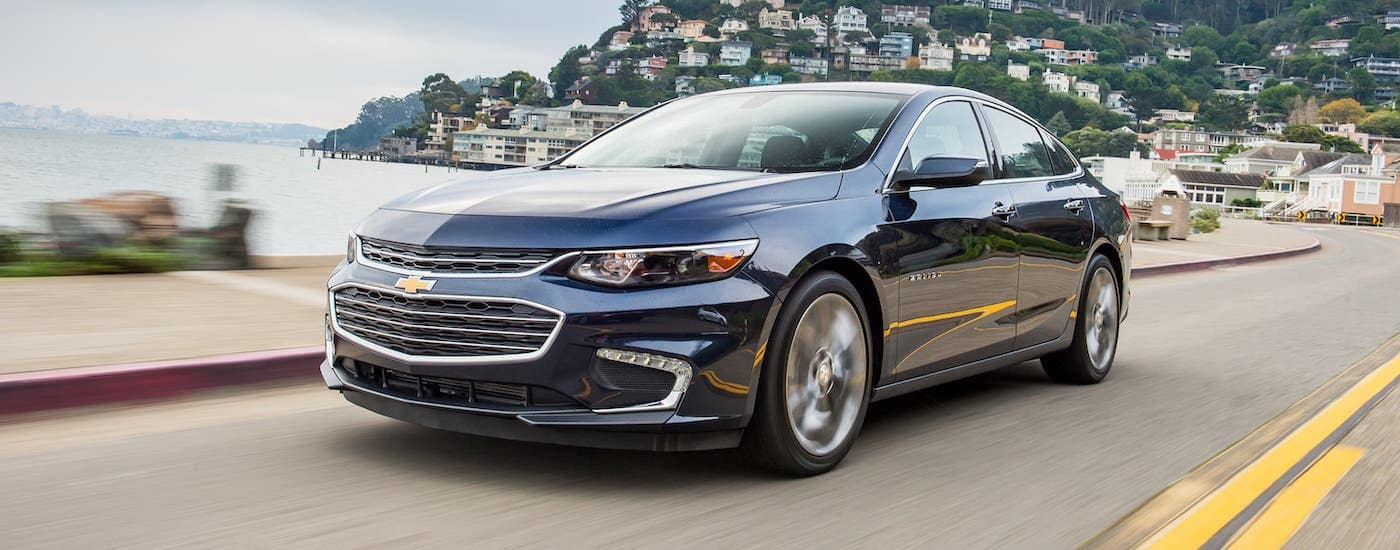 A dark blue 2016 Chevy Malibu driving by an body of water