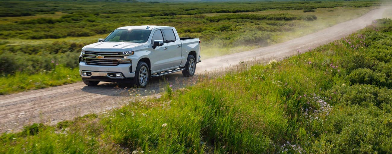 A white 2020 Chevy Silverado, which wins when comparing the 2020 Chevy Silverado vs 2020 Toyota Tundra, is driving on a dirt road outside of Cincinnati, OH.
