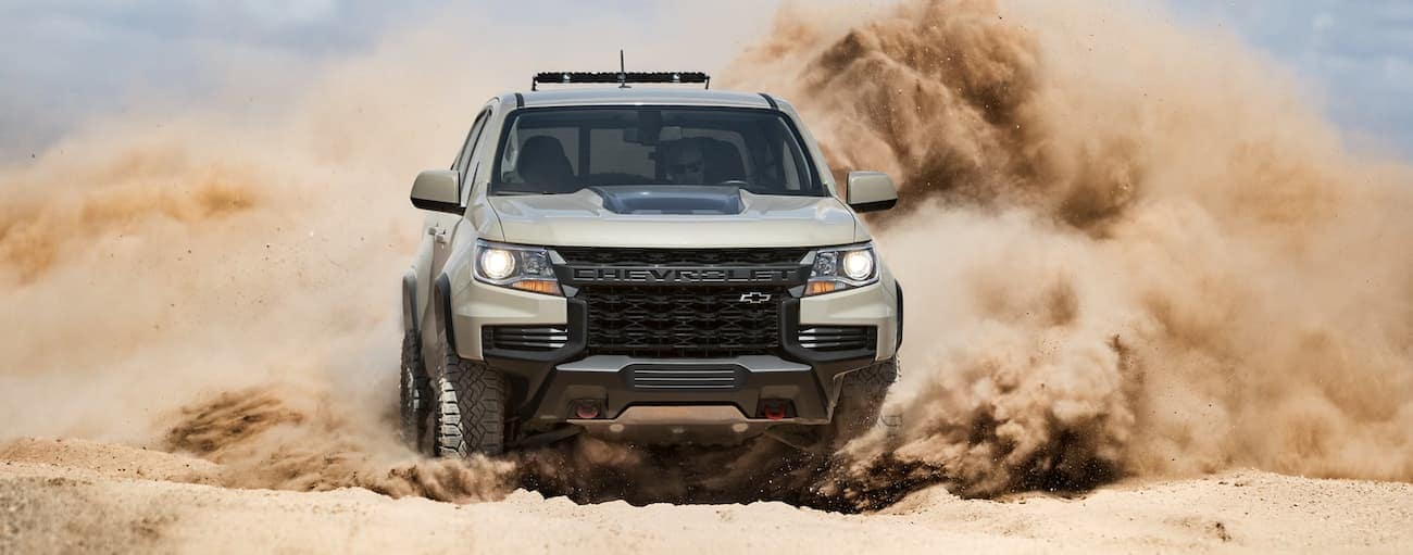 A tan 2021 Chevy Colorado ZR2 is racing in the dirt near Cincinnati, OH.