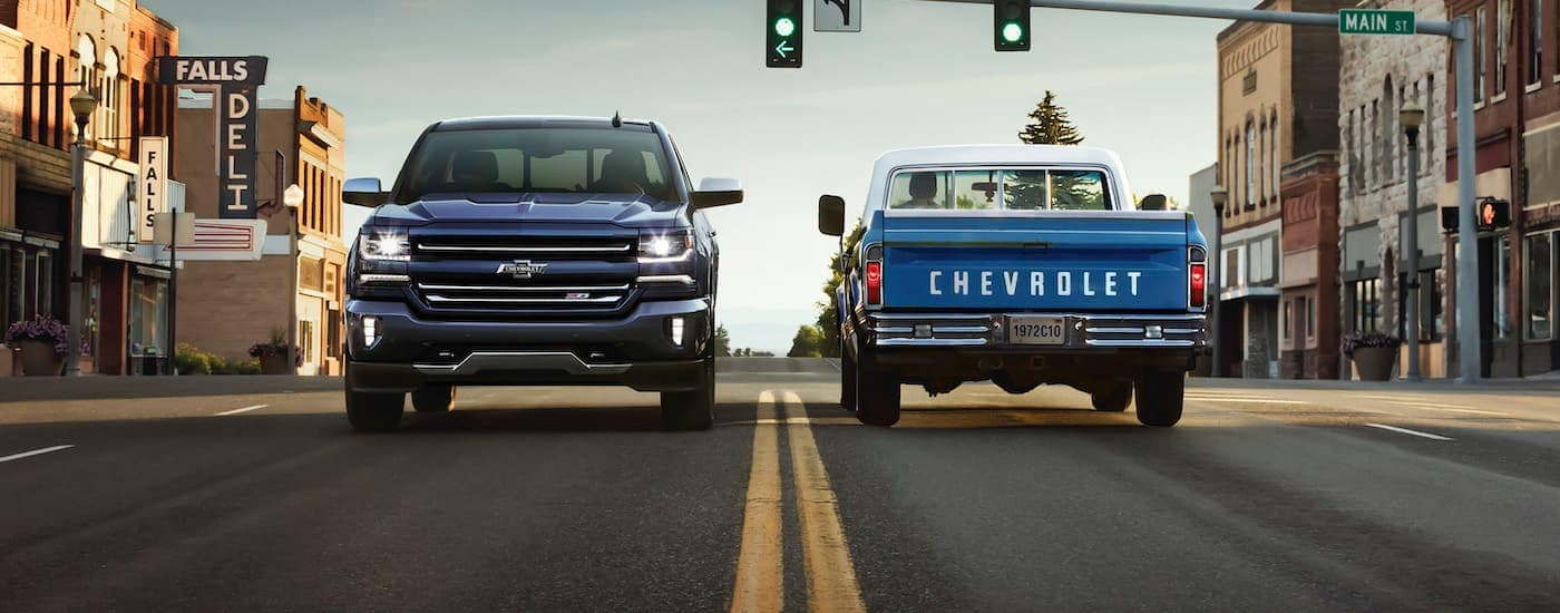 A blue 2018 Chevy Silverado is stopped at a light next to one of the blue C10 Chevy models.