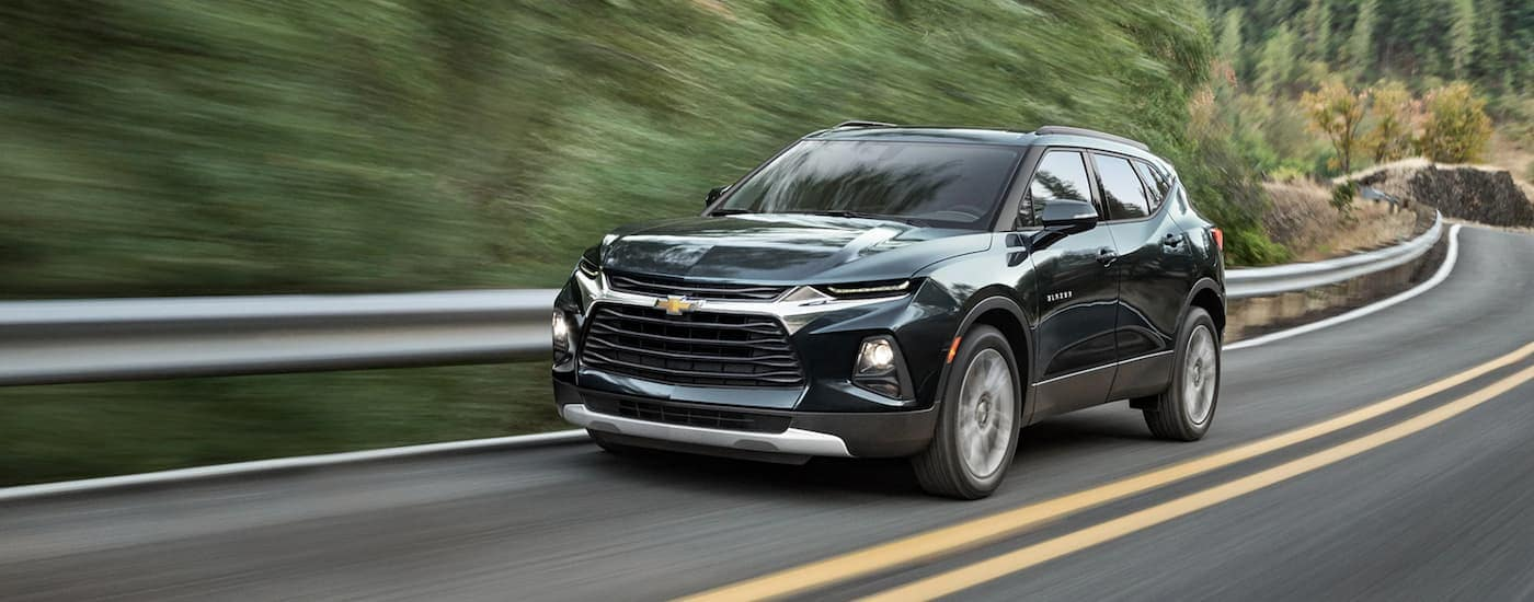 A dark green 2020 Chevy Blazer is driving on a tree-lined road near Cincinnati, OH.