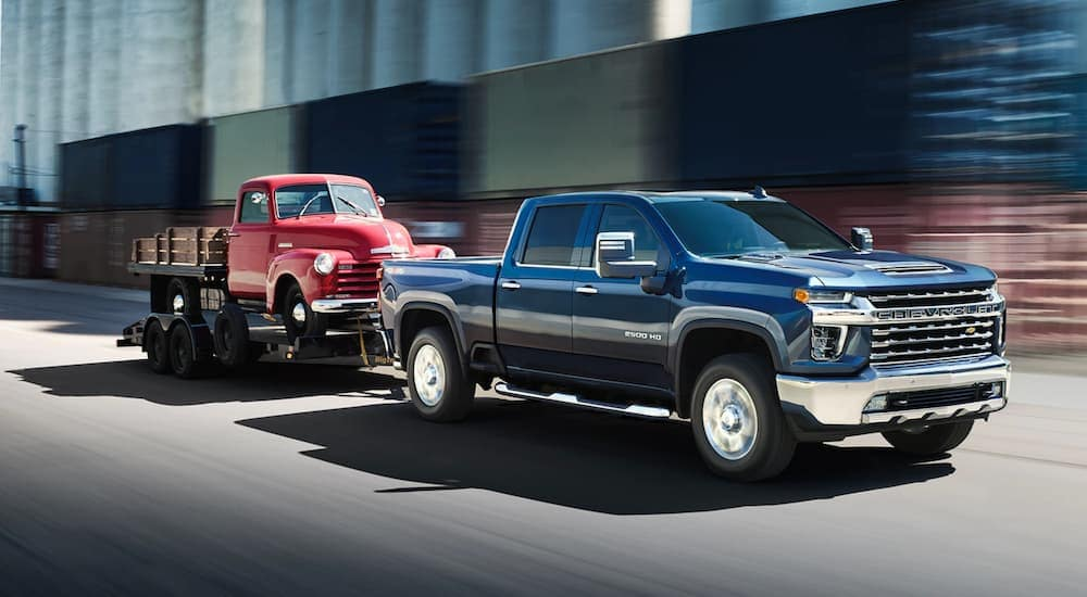 A dark blue 2020 Chevy Silverado 2500HD is towing an antique Chevy truck.