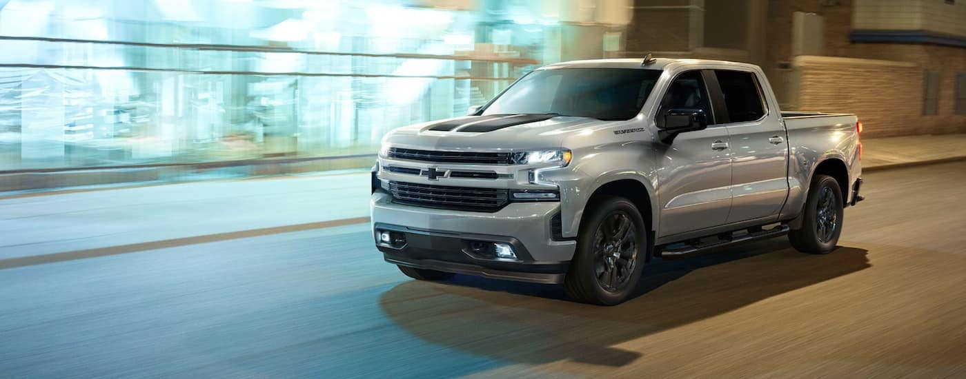A silver 2020 Chevy Silverado RST Rally with black racing stripes is driving on a city street at night.