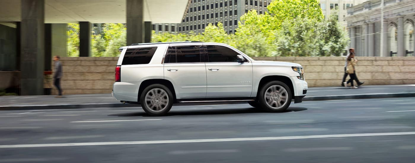 A white 2020 Chevy Tahoe, which is popular among Chevy models, is driving on a city street.