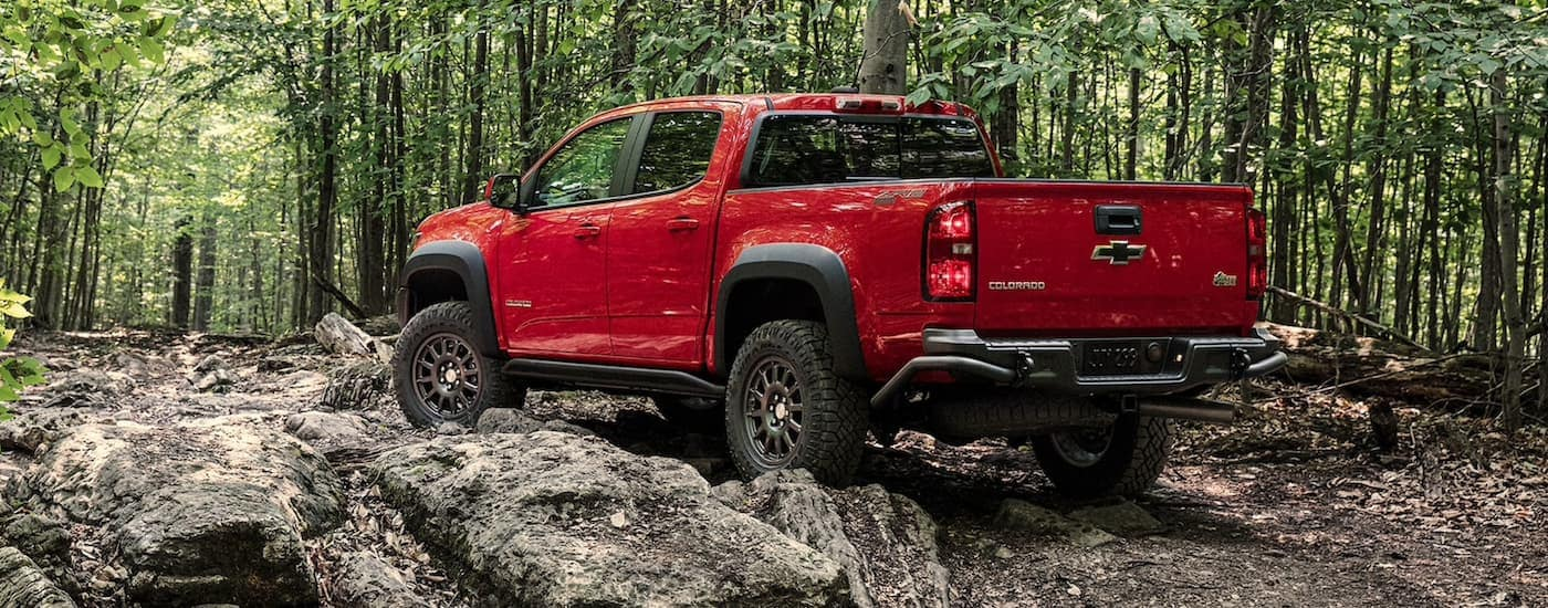 A red 2020 Chevy Colorado ZR2 is off-roading in the woods.