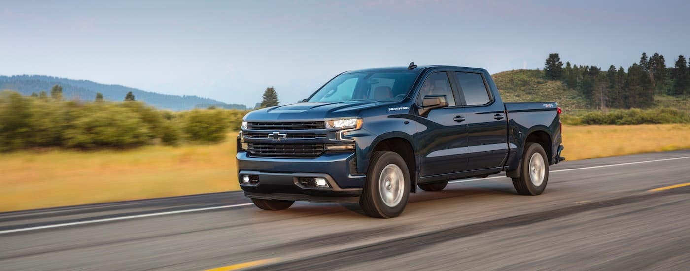 A dark blue 2020 Chevy Silverado is driving on a highway with hills in the distance.